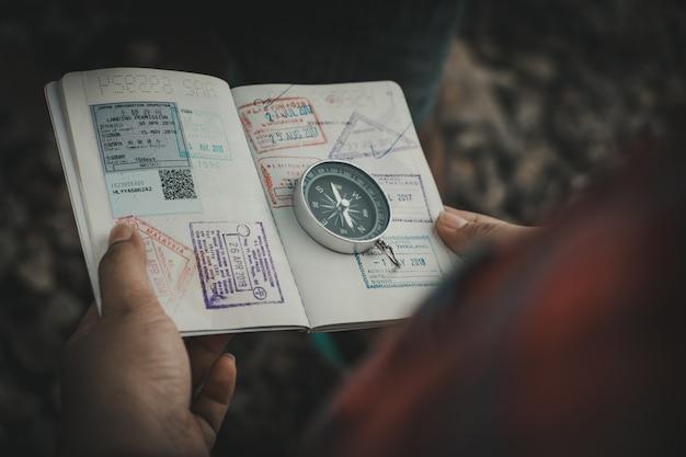 Ręka trzyma paszport kompasu, aby znaleźć miejsca podróży. zabytkowy styl.