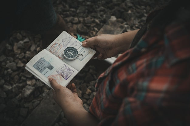Ręka trzyma paszport kompasu, aby znaleźć miejsca podróży.