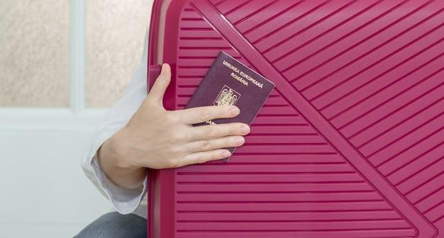 Ręka trzyma paszport rumuński na tle różowej walizki i gotowy do podróży.