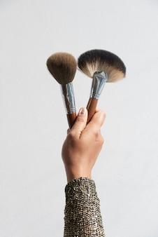 Ręka trzyma pędzle do makijażu