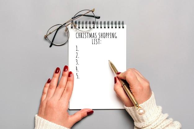 Ręka trzyma pióro, pisanie listy świątecznych zakupów, pomysły na prezenty na biały notatnik na szaro