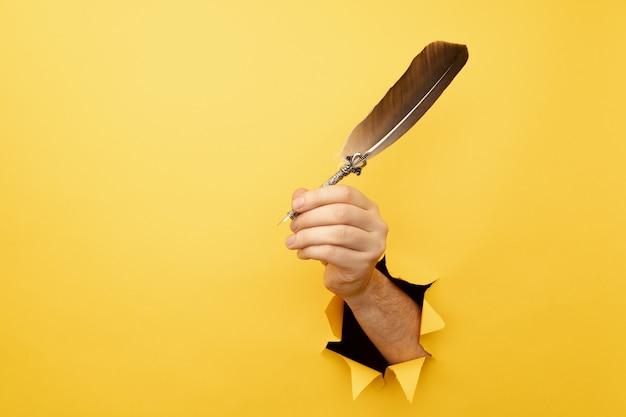 Ręka trzyma pióro z żółtego podartego papieru.