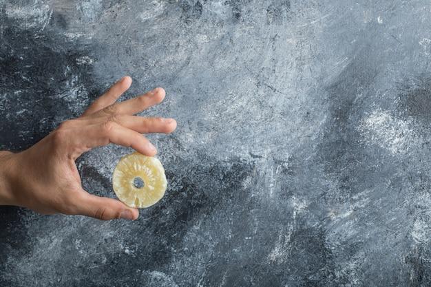 Ręka trzyma plasterek suszonego ananasa na szarym tle.