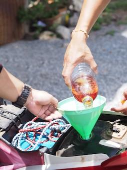 Ręka trzyma plastikową butelkę paliwa i wypełnienie motocykla