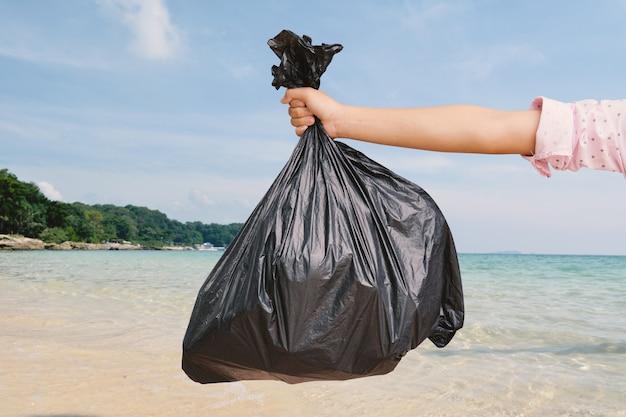 Ręka trzyma plastikową torbę na śmieci na brzegu morza