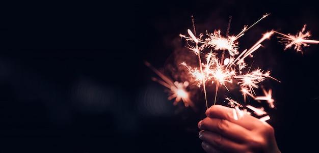 Ręka trzyma płonącego sparkler wybuch na czarnym bokeh