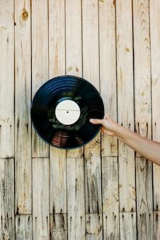 Ręka trzyma płyta winylowa na drewniane tła