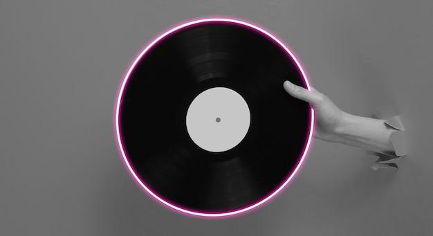 Ręka trzyma płytę winylową z neonowym kółkiem przez rozdarty papier