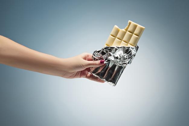 Ręka trzyma płytkę białej czekolady