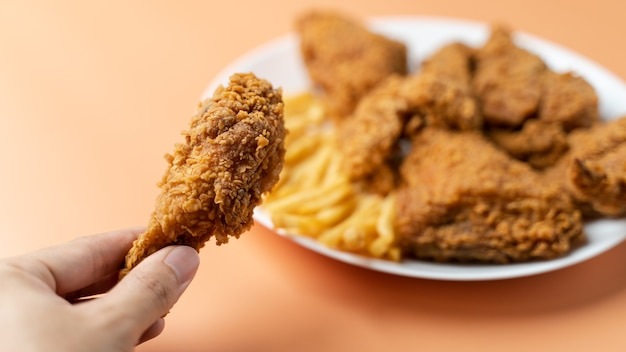 Ręka trzyma podudzia, chrupiący smażony kurczak z frytkami w białym talerzu na pomarańczowym tle.