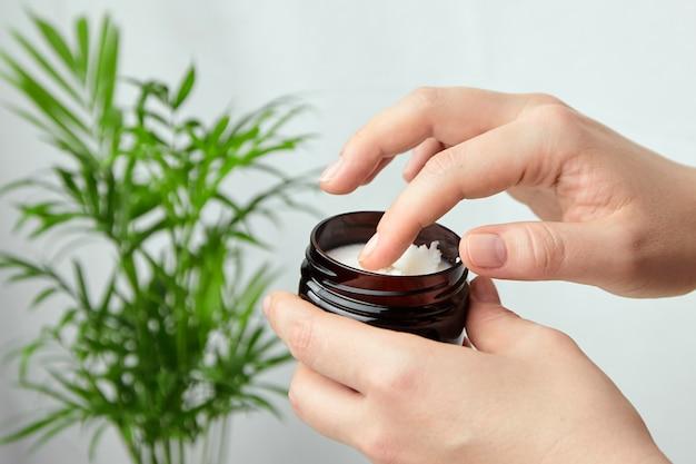 Ręka trzyma pojemnik z białym kremem wygładzająco-łagodzącym przeciwzmarszczkowym