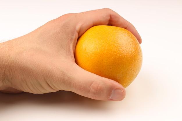 Ręka trzyma pomarańczę na białym