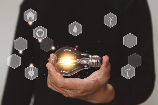 Ręka trzyma pomysł na żarówkę ze środowiskiem i innowacjami