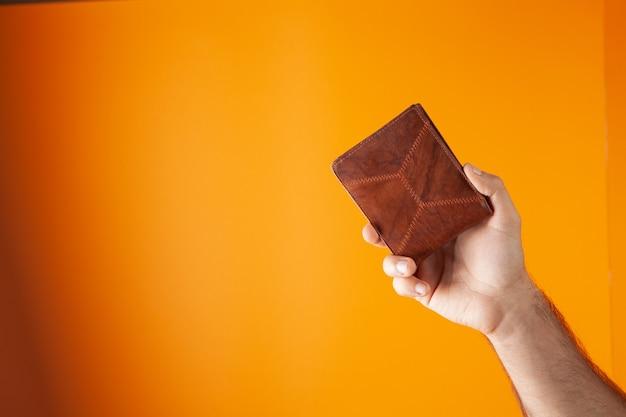 Ręka trzyma portfel na pomarańczowym tle