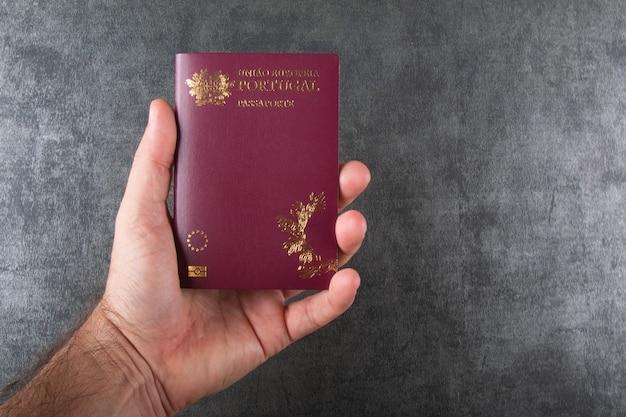 Ręka trzyma portugalski paszport z szarym tłem.