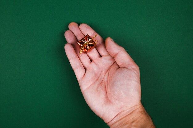 Ręka trzyma prezent noworoczny na zielonym tle.