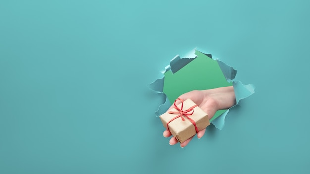 Ręka trzyma prezent rzemieślniczy przez rozdarty otwór papieru.