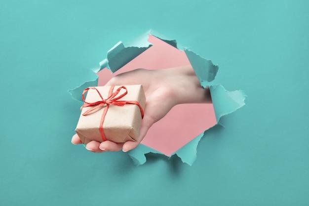 Ręka trzyma prezent rzemiosła przez rozdarty papierowy otwór. oferta specjalna, wyprzedaż, bonus, prezent