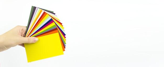 Ręka trzyma próbki kolorów. paleta kolorów. przewodnik po próbkach farb.