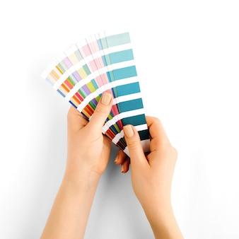 Ręka trzyma próbki kolorów. paleta trendów kolorystycznych. płaski świeckich, widok z góry.