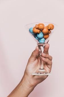 Ręka trzyma przezroczyste szkło z kolorowymi kulkami