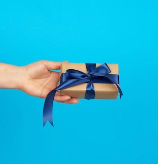 Ręka trzyma pudełko z prezentem owinięte w brązowy papier pakowy i przewiązane jedwabną niebieską wstążką