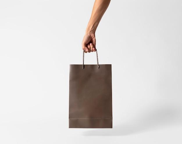 Ręka trzyma pustą brązową papierową torbę na makieta szablon reklamy i marki na szarym tle.