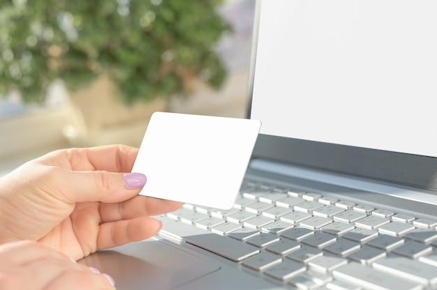 Ręka trzyma pustą kartę kredytową nad laptopem z pustym ekranem dla makiety