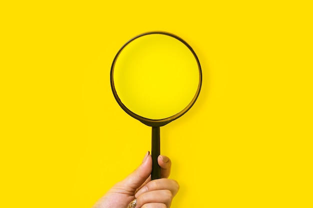 Ręka trzyma pustą lupę na żółto
