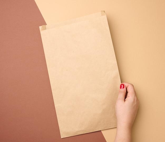 Ręka trzyma pustą papierową torbę z brązowego papieru kraft na brązowym tle, z bliska