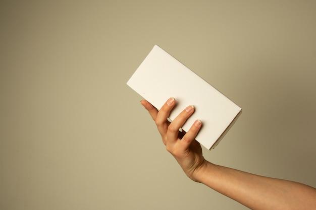 Ręka trzyma puste białe pudełko, makieta. kopia przestrzeń. koncepcja pakowania i dostawy.