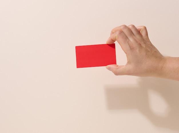 Ręka trzyma pusty czerwony papier na beżowym tle. skopiuj, wklej obraz lub tekst, z bliska