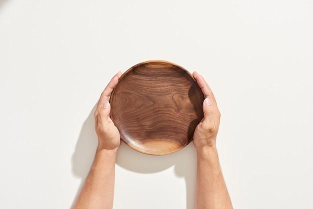 Ręka trzyma pusty drewniany talerz na białym tle