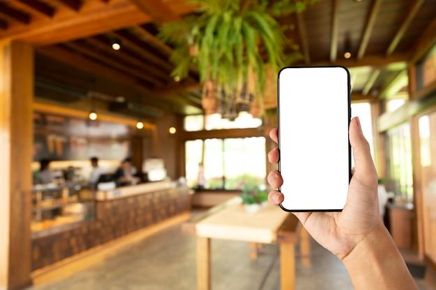 Ręka trzyma pusty ekran smartfona w kawiarni.