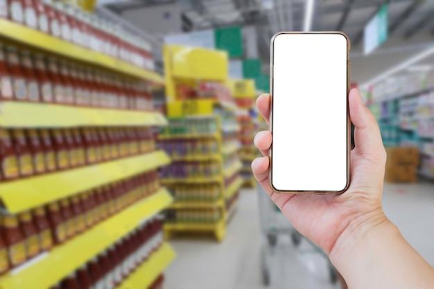 Ręka trzyma pusty ekran smartfona w supermarkecie
