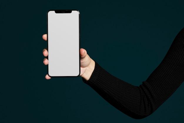 Ręka trzyma pusty ekran smartfona z przestrzenią projektową