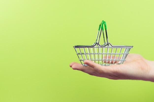 Ręka trzyma pusty metalowy kosz na zakupy. pojęcie konsumpcjonizmu, symbol zakupów