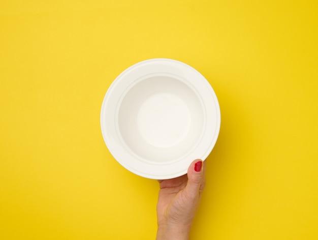 Ręka trzyma pusty okrągły talerz na żółtym tle, widok z góry
