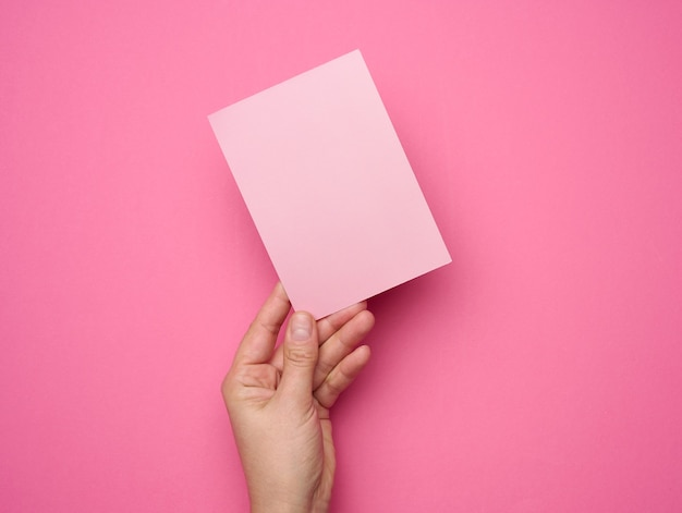 Ręka trzyma pusty różowy papier na różowym tle. skopiuj, wklej obraz lub tekst, z bliska
