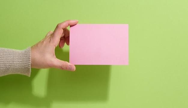 Ręka trzyma pusty różowy papier na zielonym tle. skopiuj, wklej obraz lub tekst, z bliska