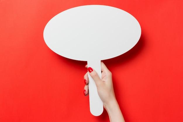 Ręka trzyma pusty transparent makiety na czerwonym tle na białym tle