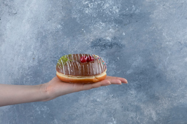 Ręka trzyma pyszną czekoladę posypuje pączka na powierzchni marmuru.