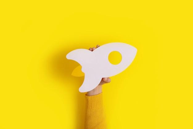 Ręka trzyma rakietę na modnym żółtym tle, pomysł na start