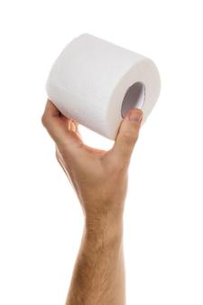 Ręka trzyma rolkę papieru toaletowego na białym tle