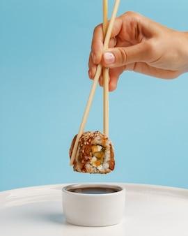 Ręka trzyma rolkę sushi drewnianymi patyczkami.