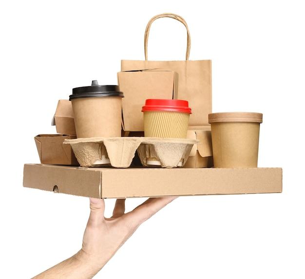 Ręka trzyma różne pojemniki na żywność na wynos, pudełko po pizzy, filiżanki do kawy w uchwycie i papierową torbę na białym tle. dostawa jedzenia