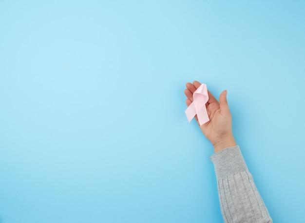 Ręka trzyma różową wstążkę w kształcie łuku na niebieskiej powierzchni