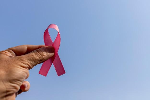 Ręka trzyma różowy łuk, reprezentujący miesiąc zapobiegania rakowi piersi. różowy październik