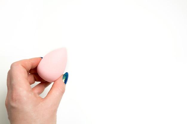 Ręka trzyma różowy piękno blender na białym tle. miejsce na tekst