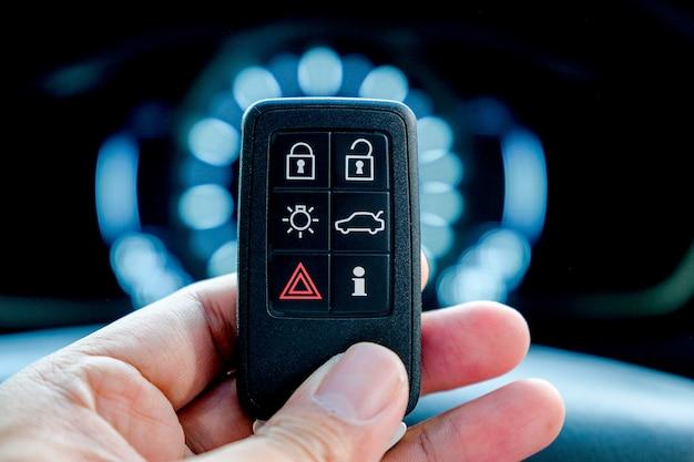 Ręka trzyma samochód inteligentny pilot bezkluczykowy, inteligentne urządzenie technologiczne.